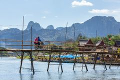 Wooden bridge across Nam Song river at Vang Vieng, Laos. Vang Vieng, Laos - January 19, 2017: Wooden bridge across Nam Song river at Vang Vieng, Laos royalty free stock photos