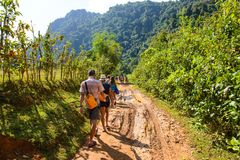 Vang Vieng, Laos - 13. November 2014: Reisender, der mit Schlammstraße zu Tham Nam Vang Vieng, Lao geht Stockfoto