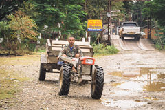 VANG VIENG, LAOS - OCT 24. An unidentified man driving tractor on a rural road on oct 24, 2014, in Vang Vieng, Laos. Vang Vieng is a tourism-oriented town in Royalty Free Stock Image