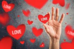 Vangend rode Valentijnskaartenharten met gedrukte woordliefde Royalty-vrije Stock Foto