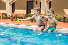 Vangt kleine leuke jongen twee een stuk speelgoed vis in de pool stock foto's