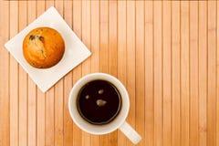 Vaniglia con i muffin di pepita di cioccolato con una tazza di caffè Fotografia Stock