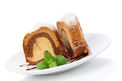 Vanilj- och chokladkaka med isolerade mintkaramelllaves Arkivbild