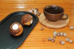 Vanilj- och chokladmuffin med en kopp kaffe, muttrar och kanel Arkivbilder