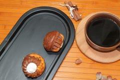 Vanilj- och chokladmuffin med en kopp kaffe, muttrar och kanel Arkivfoton