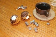 Vanilj- och chokladmuffin med en kopp kaffe, muttrar och kanel Fotografering för Bildbyråer