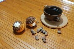 Vanilj- och chokladmuffin med en kopp kaffe, muttrar och kanel Royaltyfri Bild