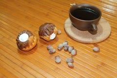 Vanilj- och chokladmuffin med en kopp kaffe, muttrar och kanel Arkivfoto