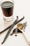 Vaniljbönor och kopp med extracten Arkivfoton