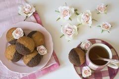 Vaniljchokladmuffin p? den rosa plattan och servett, kopp te och rosor p? den vita tabellen royaltyfria foton