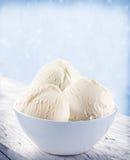 Vaniljglassskopor i den vita koppen. Arkivfoton