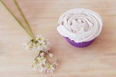 Vaniljmuffin med den vita glasyren på kaka och blommor på en tabell Royaltyfri Foto