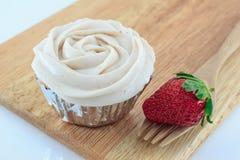 Vaniljmuffin med jordgubbeglasyr på kaka och den nya jordgubben Royaltyfria Bilder