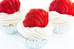 Vaniljmuffin med jordgubbeglasyr på kaka och den nya jordgubben Royaltyfri Foto
