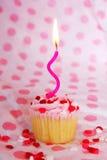 Vaniljmuffin med rosa glasyr på kaka och stearinljuset Royaltyfri Foto