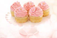 Vaniljmuffin med rosa hallonglasyr på kaka Arkivfoto