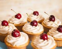 Vaniljmuffin med smör lagar mat med grädde glasyr på kaka och en körsbär överst Arkivbilder