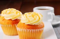 Vaniljmuffin som duggas med karamellsås Arkivfoto