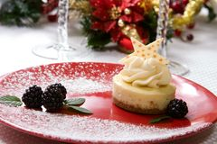 Vanilla Bean Cheesecake. Delicious Vanilla Bean Cheesecake served with fresh blackberries and mint. Christmas ornament out of focus in background Royalty Free Stock Image