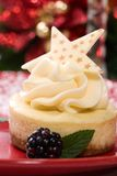 Vanilla Bean Cheesecake. Delicious Vanilla Bean Cheesecake served with fresh blackberries and mint. Christmas ornament out of focus in background Stock Image
