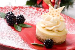 Vanilla Bean Cheesecake. Delicious Vanilla Bean Cheesecake served with fresh blackberries and mint. Christmas ornament out of focus in background Royalty Free Stock Photography