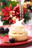 Vanilla Bean Cheesecake. Delicious Vanilla Bean Cheesecake served with fresh blackberries and mint. Christmas ornament out of focus in background Royalty Free Stock Photo