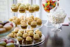 Vanilla bean mini cupcakes decorated with cyan and pink candy beads on a clear tiered tray on a dessert table with marshmallows, j Stock Photo