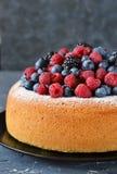 Vanilla cake with creamy cream and berries: blueberries, raspberries and blackberries on a concrete background. stock image