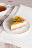 Vanilla cheesecake on a white plate and cup of tea, vertical Royalty Free Stock Photos