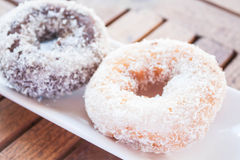 Vanilla and chocolate coconut donuts on wooden table Royalty Free Stock Photo