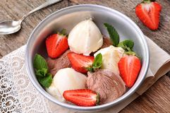 Vanilla and chocolate ice cream with organic strawberries. Rustic style. Royalty Free Stock Photography