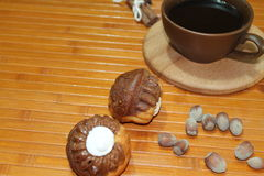 Vanilla and chocolate muffins with a cup of coffee, nuts, and cinnamon Royalty Free Stock Image