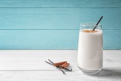 Vanilla and cinnamon protein shake in glass. On table royalty free stock photo