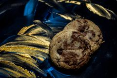 Vanilla cookies with chocolate chips on a blue and gold background stock images