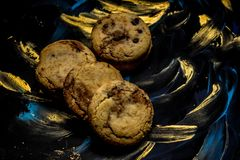 Vanilla cookies with chocolate chips on a blue and gold background stock photography