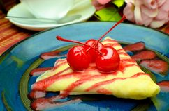Vanilla crape cake on dish with strawberry jam and cherry Stock Photo