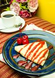 Vanilla crape cake on dish with strawberry jam and cherry Stock Image