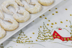 Vanilla crescents on a Christmas tablecloth. On a Christmas tablecloth presented a plate vanilla crescent Stock Photos
