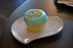 Vanilla cupcake with blue icing. A vanilla cupcake with blue buttercream frosting and sprinkles on a white plate Stock Images