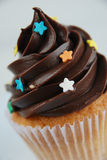 Vanilla cupcake with chocolate cover. Decorated with sugar stars Royalty Free Stock Image