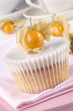Vanilla cupcake with icing and physalis Royalty Free Stock Images