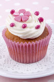 Vanilla cupcake with pink flower. And red chocolate beans Stock Image