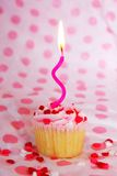 Vanilla cupcake with pink frosting and candle Royalty Free Stock Photo