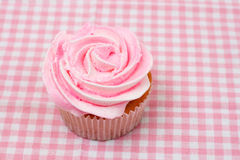 Vanilla cupcake with pink rose icing. Fresh vanilla cupcake with pink rose icing on checkered background Royalty Free Stock Photos