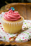 Vanilla cupcake with strawberry butter cream. On napkin against wooden backdrop stock image