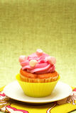 Vanilla cupcake with strawberry icing. Fresh vanilla cupcake in green cup with strawberry icing and marshmallows on decorative background Royalty Free Stock Photo