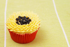 Vanilla cupcake with sunflower decoration. Fresh vanilla cupcake with sunflower buttercream icing decoration on green background Stock Photography