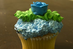 Vanilla cupcake topped with Blue and Green frsoting,and a Blue sugar rose Stock Photo