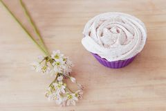 Vanilla cupcake with white frosting and flowers on a table. Vanilla cupcake with white lime frosting and flowers on a table Royalty Free Stock Photo