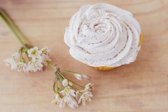 Vanilla cupcake with white frosting and flowers on a table. Vanilla cupcake with white lime frosting and flowers on a table Stock Photo